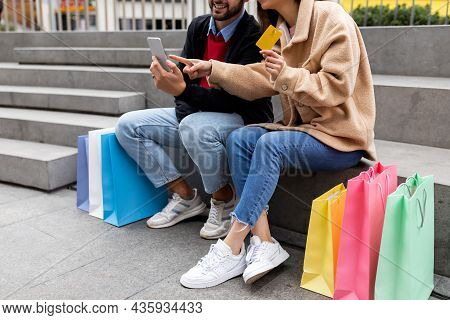 Cropped View Of Young Couple With Shopper Bags, Smartphone And Credit Card Sitting On Stairs Outdoor