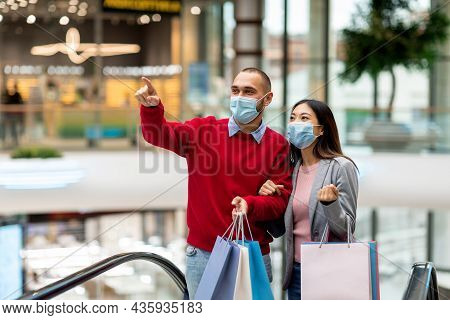 Millennial Diverse Couple Wearing Protective Masks While Shopping At Supermarket, Holding Shopper Ba
