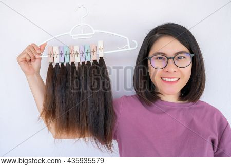 Young Asian Woman Holding A Hanger With Group Of Cutting Hair For Donation. Usable Hair Can Turn You