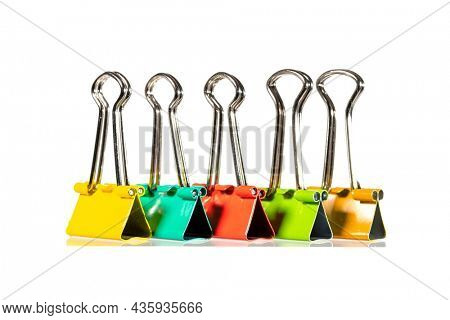 Colorful paper clips arranged in a row on white background