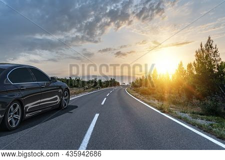 Black Car On A Scenic Road. Car On The Road Surrounded By A Magnificent Natural Landscape In The Ray