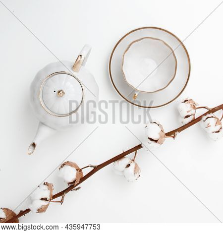 Cotton Branch On White Background And Tea-set. Flat Lay, Top View. Minimal Style. Minimalist Fashion