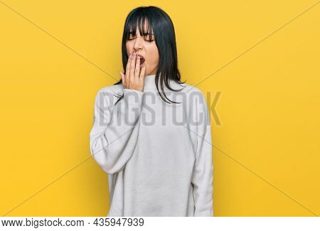 Young brunette woman with bangs wearing casual turtleneck sweater bored yawning tired covering mouth with hand. restless and sleepiness.