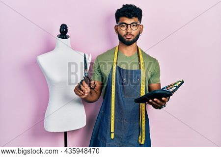 Arab man with beard dressmaker designer holding scissors and sewing kit relaxed with serious expression on face. simple and natural looking at the camera.