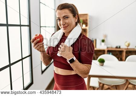 Middle age caucasian sporty woman eating apple at home.