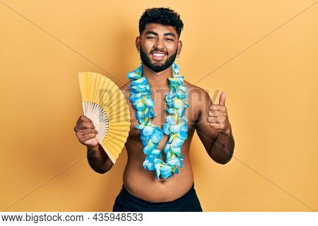 Arab man with beard wearing hawaiian lei holding handfan smiling happy and positive, thumb up doing excellent and approval sign