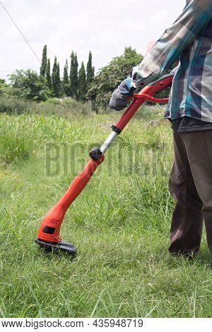Gardener Using A Lawn Trimmer Mower Cutting Grass In The Garden