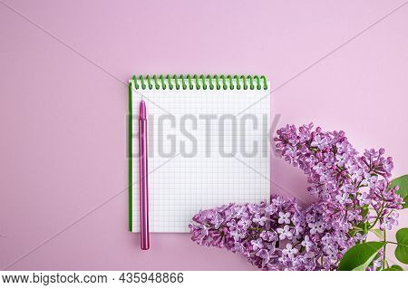 Lilac Branch And Notepad On A Pink Background. Notebook With Bright Lilac. Postcard For Loved Ones,