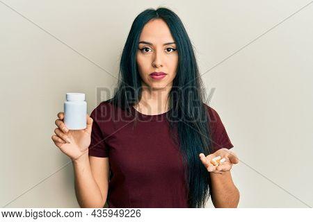 Young hispanic girl holding pills relaxed with serious expression on face. simple and natural looking at the camera.