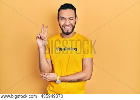 Hispanic man with beard wearing t shirt with happiness word message smiling with happy face winking at the camera doing victory sign with fingers. number two.