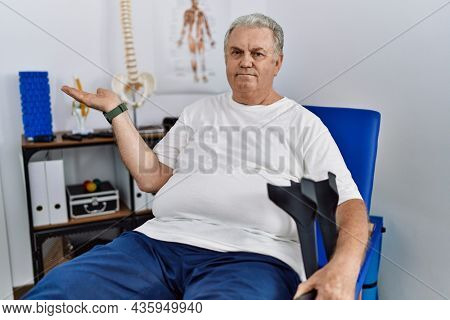 Senior caucasian man at physiotherapy clinic holding crutches smiling cheerful presenting and pointing with palm of hand looking at the camera.