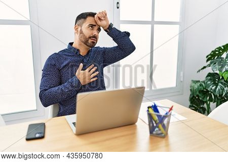 Young hispanic man with beard working at the office with laptop touching forehead for illness and fever, flu and cold, virus sick