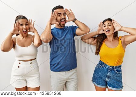 Group of young hispanic people standing over isolated background smiling cheerful playing peek a boo with hands showing face. surprised and exited
