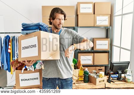 Handsome middle age man holding donations box for charity at volunteer stand looking at the watch time worried, afraid of getting late