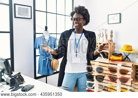 African young woman working as manager at retail boutique smiling cheerful offering hands giving assistance and acceptance.