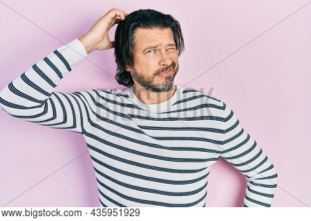 Middle age caucasian man wearing casual clothes confuse and wonder about question. uncertain with doubt, thinking with hand on head. pensive concept.