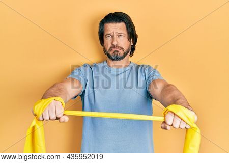 Middle age caucasian man wearing sportswear and arm elastic band depressed and worry for distress, crying angry and afraid. sad expression.