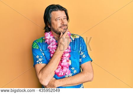 Middle age handsome man wearing summer shirt and hawaiian lei smiling looking confident at the camera with crossed arms and hand on chin. thinking positive.