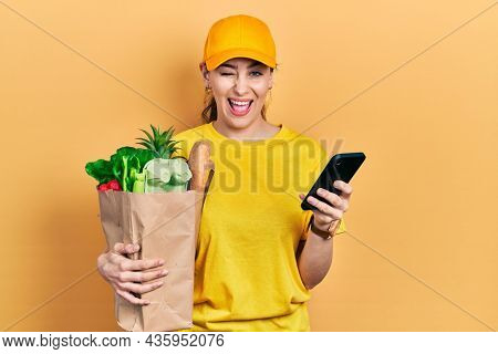 Young hispanic woman holding bag of groceries using smartphone winking looking at the camera with sexy expression, cheerful and happy face.