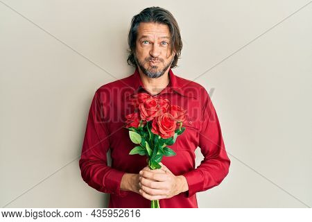 Middle age handsome man holding bouquet of red roses puffing cheeks with funny face. mouth inflated with air, catching air.