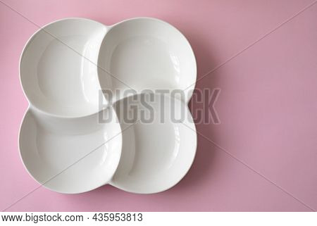 A White Four-course Dinner Plate With A Soft Shadow On A Light Pink Surface Background. Ready To Dro