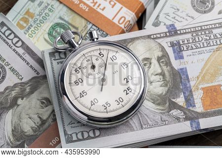 Money And Stopwatch. Dollars Banknotes And Stopwatch. Time Is Money
