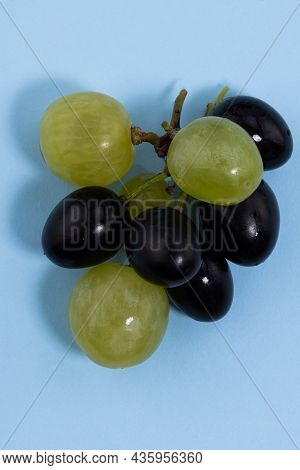 Fresh Ripe Black Grapes And Green Grapes On A Blue Background.