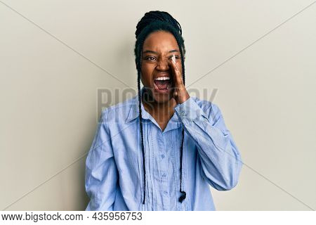 African american woman with braided hair wearing casual blue shirt shouting and screaming loud to side with hand on mouth. communication concept.