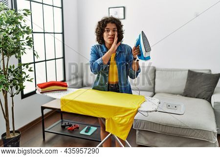 Young hispanic woman ironing clothes at home hand on mouth telling secret rumor, whispering malicious talk conversation