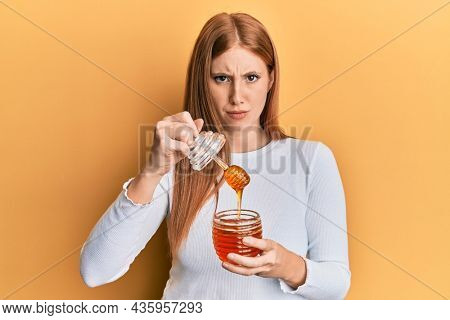 Young irish woman holding honey skeptic and nervous, frowning upset because of problem. negative person.