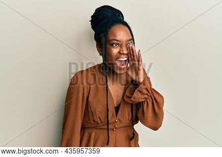 African american woman with braided hair wearing casual brown shirt shouting and screaming loud to side with hand on mouth. communication concept.