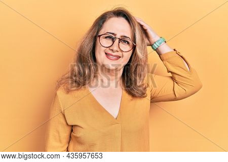 Middle age caucasian woman wearing casual clothes and glasses confuse and wonder about question. uncertain with doubt, thinking with hand on head. pensive concept.