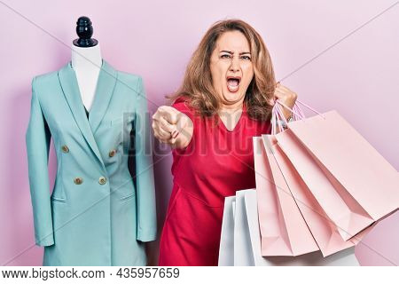 Middle age caucasian woman holding shopping bags annoyed and frustrated shouting with anger, yelling crazy with anger and hand raised
