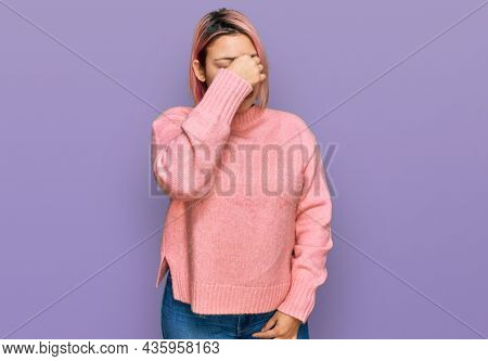 Hispanic woman with pink hair wearing casual winter sweater tired rubbing nose and eyes feeling fatigue and headache. stress and frustration concept.
