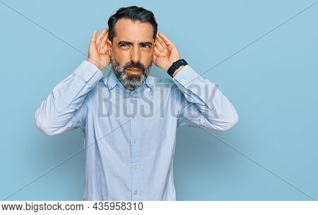 Middle aged man with beard wearing business shirt trying to hear both hands on ear gesture, curious for gossip. hearing problem, deaf