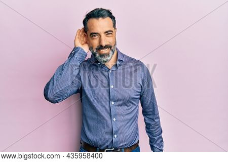 Middle age man with beard and grey hair wearing business clothes smiling with hand over ear listening an hearing to rumor or gossip. deafness concept.