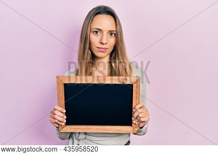 Beautiful hispanic woman holding small blackboard relaxed with serious expression on face. simple and natural looking at the camera.