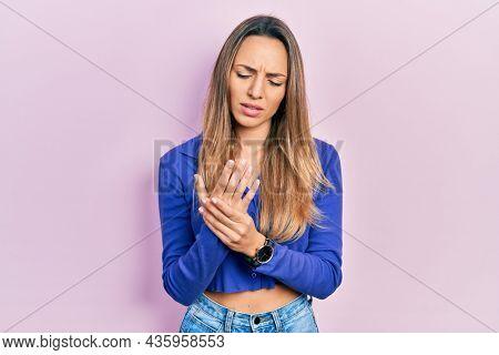 Beautiful hispanic woman wearing casual blue shirt suffering pain on hands and fingers, arthritis inflammation