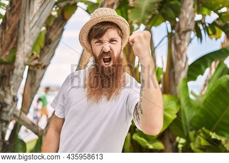 Caucasian man with long beard outdoors on a sunny day wearing summer hat annoyed and frustrated shouting with anger, yelling crazy with anger and hand raised