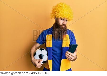 Redhead man with long beard football hooligan cheering game holding smartphone skeptic and nervous, frowning upset because of problem. negative person.
