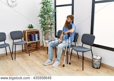 Young redhead man using crutches sitting on the chair at clinic waiting room.