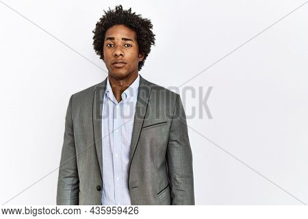 Young african american man wearing business jacket over isolated white background with serious expression on face. simple and natural looking at the camera.