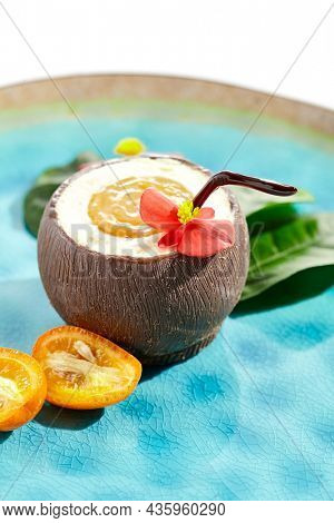 Creative summer dessert isolated on white background. Coconut from chocolate with mousse and passion fruit jelly. Coconut  and passion fruit cake in Hawaiian style. Dessert  in cocktail style