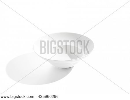 Empty white plate isolated on white background. Modern white ceramic with hard shadow. Empty tableware. White bowl in minimal style
