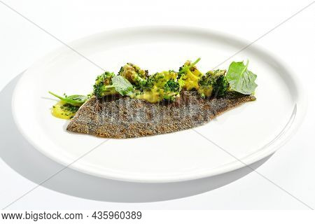 Roasted white fish with crispy skin, broccoli in beurre blanc sauce. Fried trout fillet with green vegetables in minimal style. Fish and broccoli on white plate in restaurant menu. Contemporary food