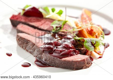 Venison steak with baked vegetables isolated on white plate. Meat steak medium rare roasted with carrot, beetroot and mashed potatoes with cherry sauce. Wild meat in restaurant menu