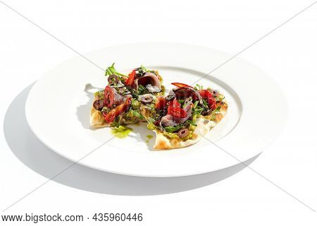 Tapas with avocado cream, anchovy, paprika and kalamata olives on focaccia. Bruschetta with guacamole and anchovy isolated on white background. Appetizer contemporary concept. Fish antipasti