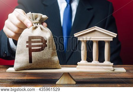 Man Puts A Philippine Peso Money Bag On Scales Next To A Bank. Taxes Payment. Lobbying Interests. St