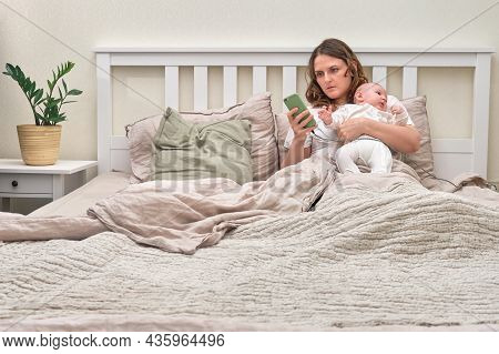 A Lonely Woman With A Newborn Baby Is Lying Alone In An Empty Bed. A Mother With A Child In Her Arms