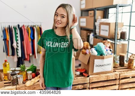 Asian young woman wearing volunteer t shirt at donations stand smiling with hand over ear listening an hearing to rumor or gossip. deafness concept.